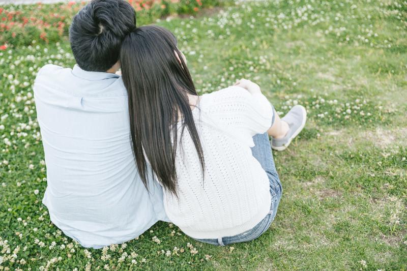 芝生の上で寄り添うカップル