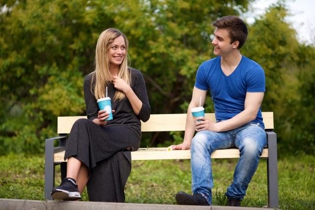 ベンチでドリンクを飲みながら話しているカップル