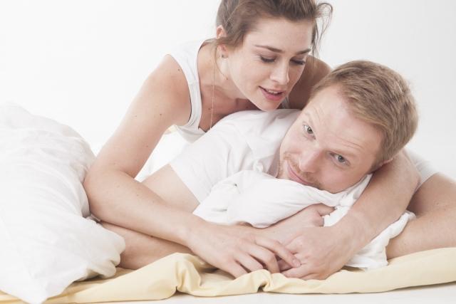 ベッドの上でくっつくカップル