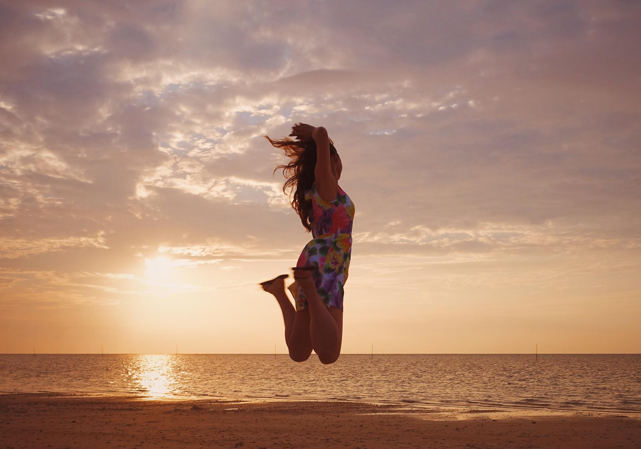 海辺でジャンプしている女性