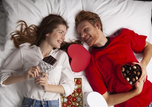 ベッドの上でチョコレートを持ちながら寝転ぶカップル
